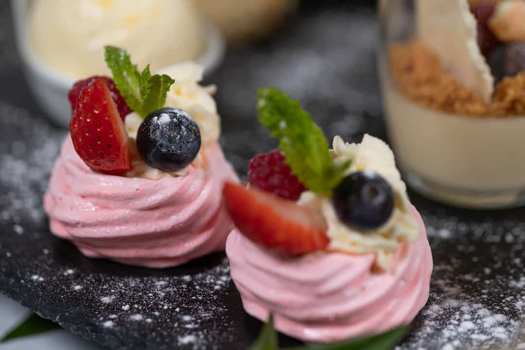 Close up of Mini Pavlova's topped with berries ready for Pink Afternoon Tea